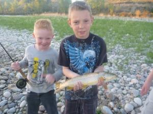 Big brother Dreyden poses with Skyler's big brown trout.